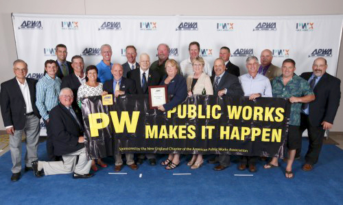 Members of the APWA New England Chapter display a 'Public Works Makes It Happen' banner at a chapter event