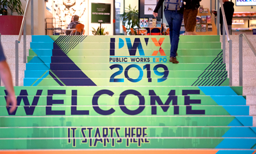 PWX Conference attendees walk up a staircase bearing a PWX graphic