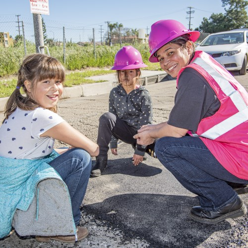 A public works professional poses with two young members of the community