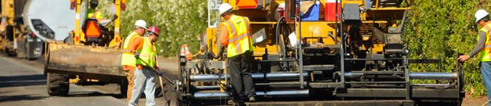 An equipment operator works as part of a road crew